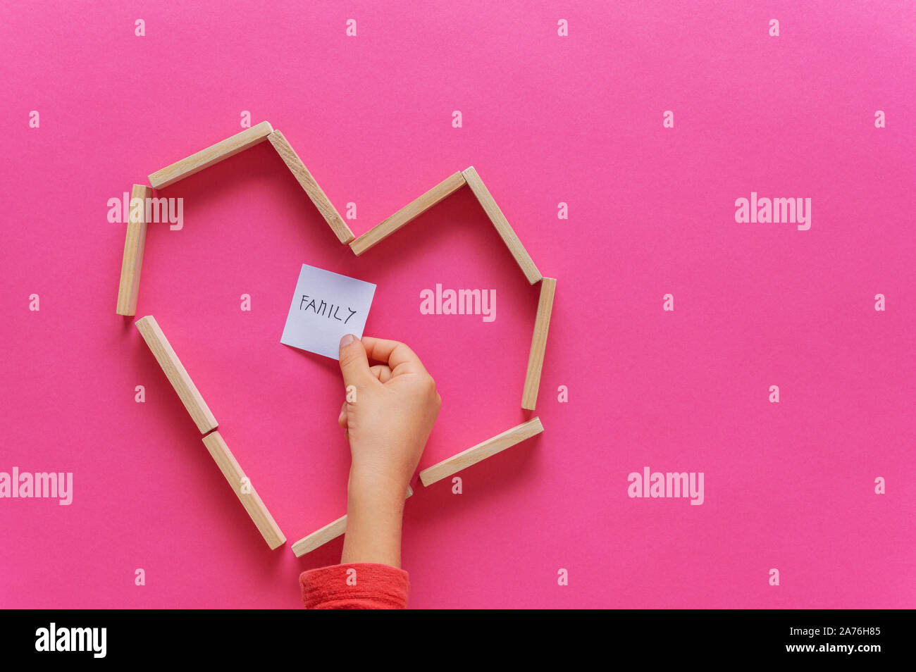 Heart shape made of wooden pegs with child hand placing post it paper with Family written on it inside the heart. Over pink background. Stock Photo