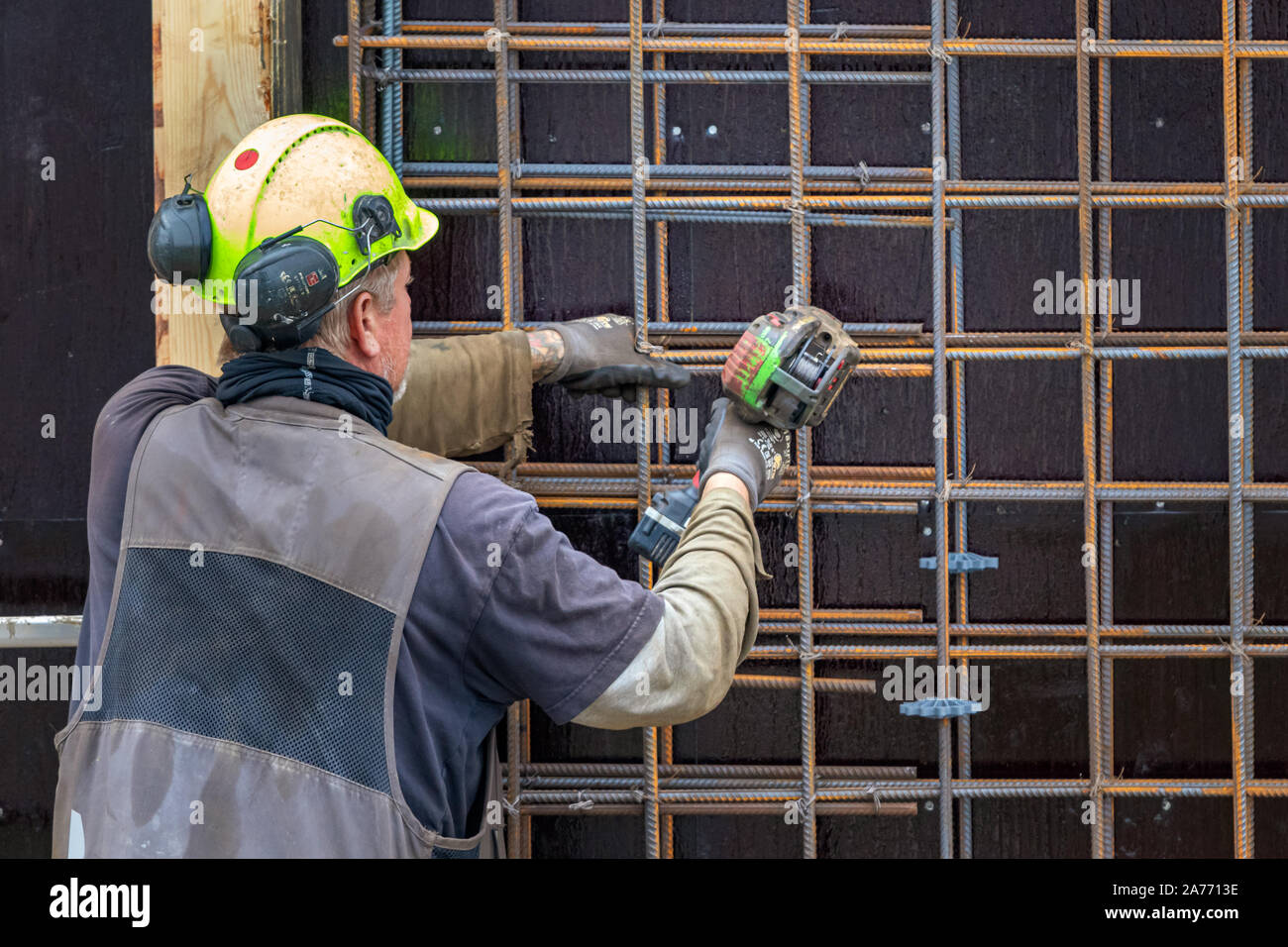 Construction worker bending - wiring concrete steel bars with a machine, outdoors in Nuuk. Stock Photo