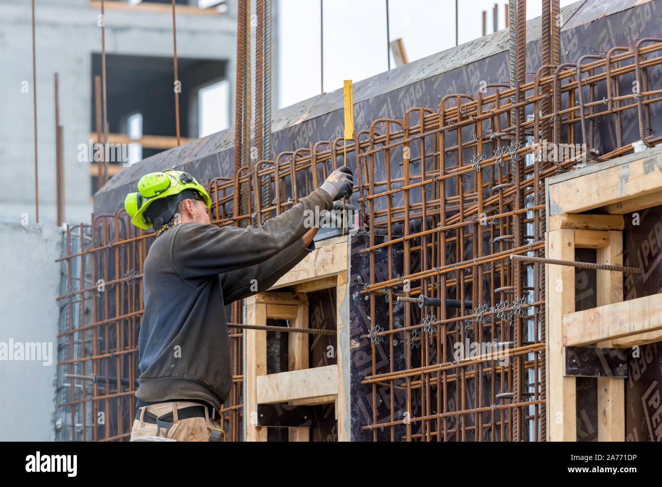 Construction worker controling the level of concrete steel bars outdoors in Nuuk. Stock Photo