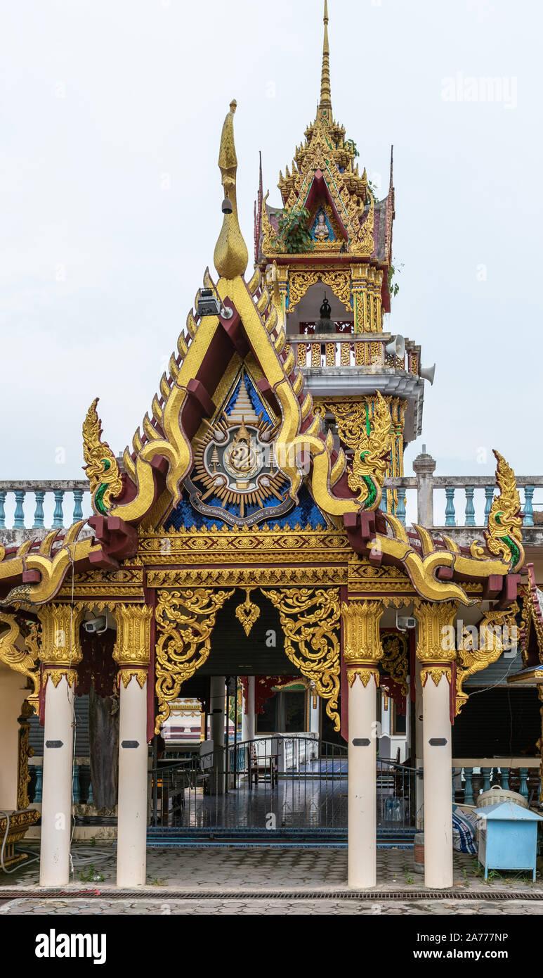 Ko Samui Island, Thailand - March 18, 2019: Wat Laem Suwannaram Chinese Buddhist Temple. Small golden shrine with blues and greens against silver sky. Stock Photo