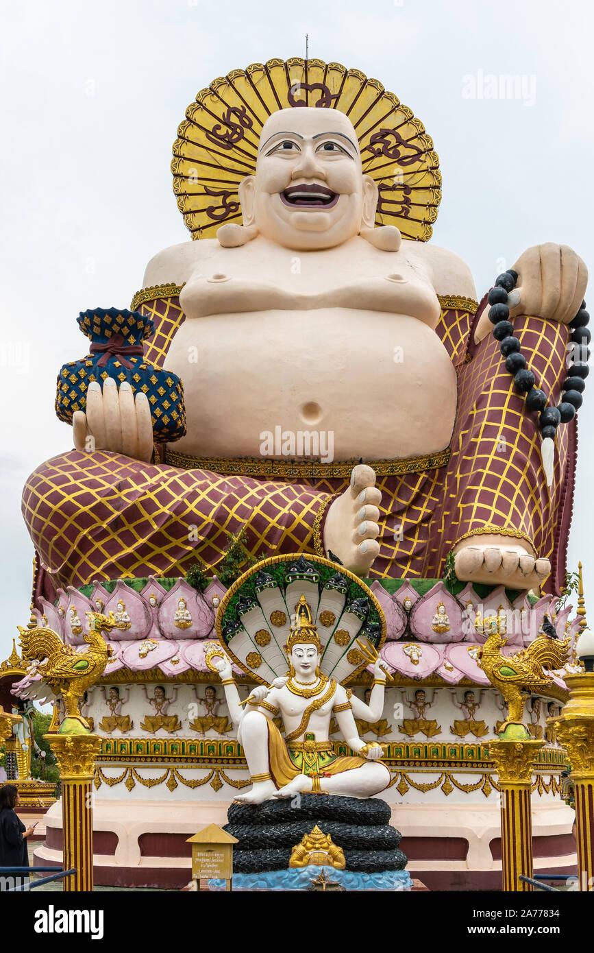 Ko Samui Island, Thailand - March 18, 2019: Wat Laem Suwannaram Chinese Buddhist Temple. Giant statue of Budai with smaller statue of Lord Vishnu on s Stock Photo