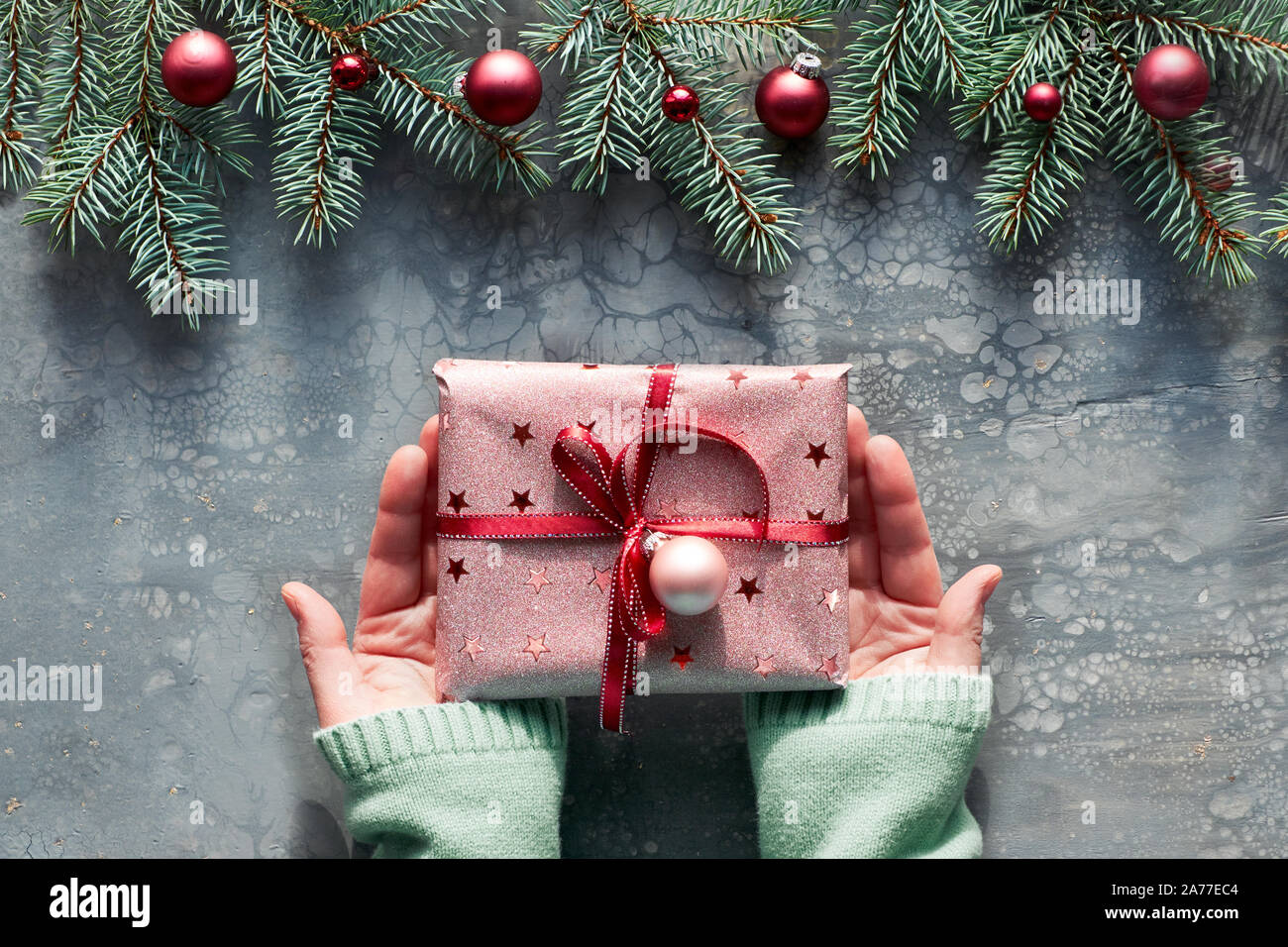 Creative Christmas Flat Lay On Grey Acrylic Fluid Art Board Female Hands In Green Mint Sweater Holding Gift Box Wrapped In Pink Paper With Red Ribbon Stock Photo Alamy