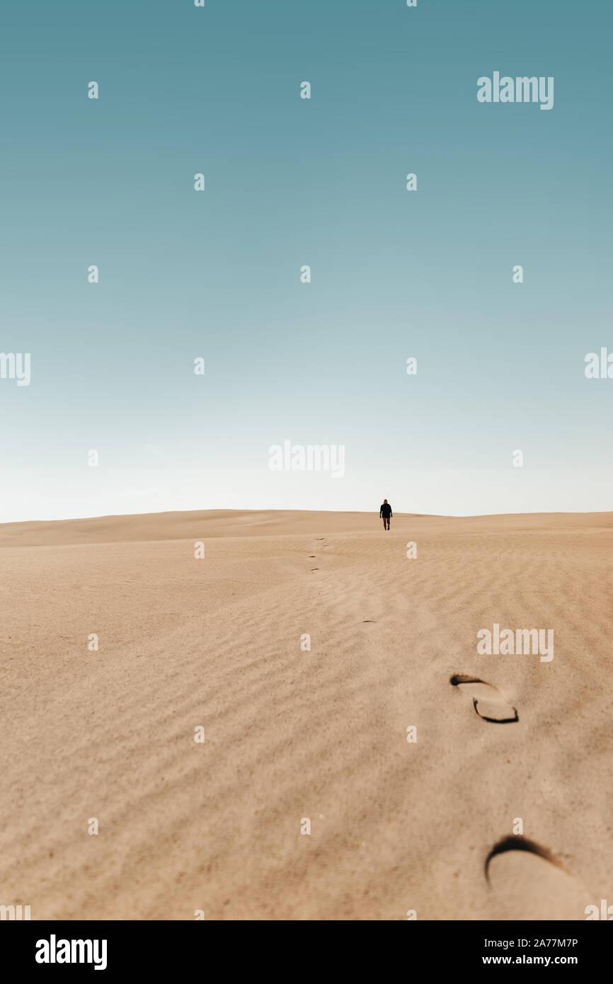 Person walks around around on a Sand Dune Desert Stock Photo