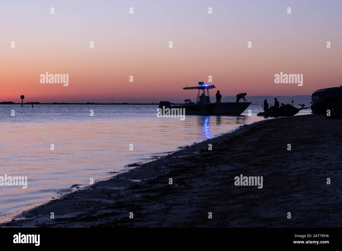 Silhouette of boat of Florida fish and wildlife officers at Dunedin Causeway in Dunedin, Florida, USA. Beautiful scenic seascape at sunset. Dunedin is Stock Photo
