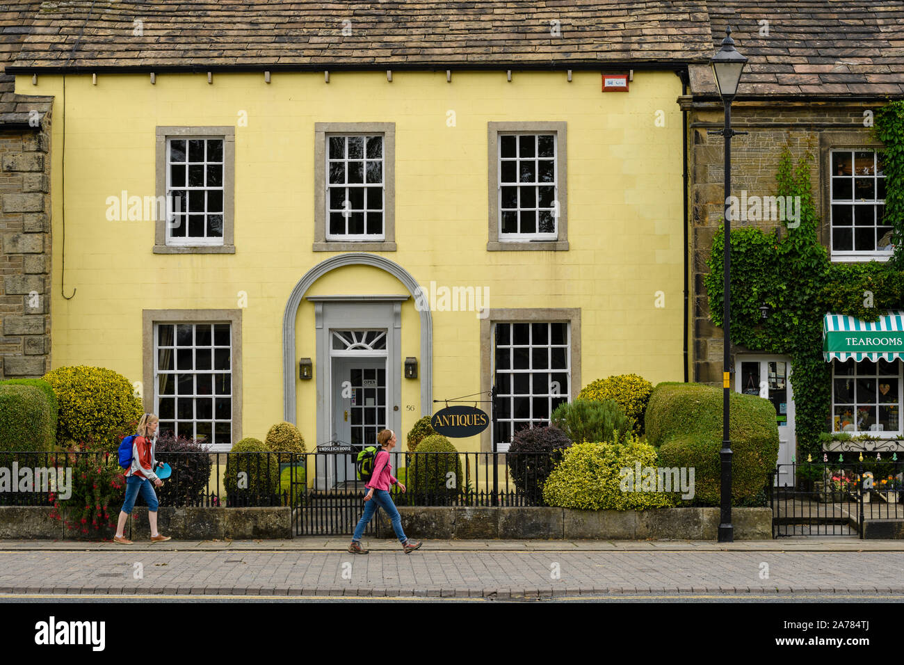 2 women walk past exterior of attractive antiques shop (Georgian building) & Dalesman Café Tearoom - village of Gargrave, North Yorkshire, England, UK Stock Photo