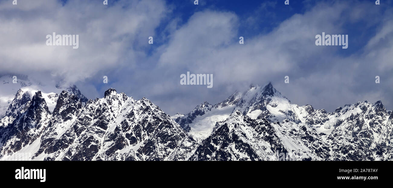 Panoramic View On Snowy Rocks And Blue Sky With Clouds At