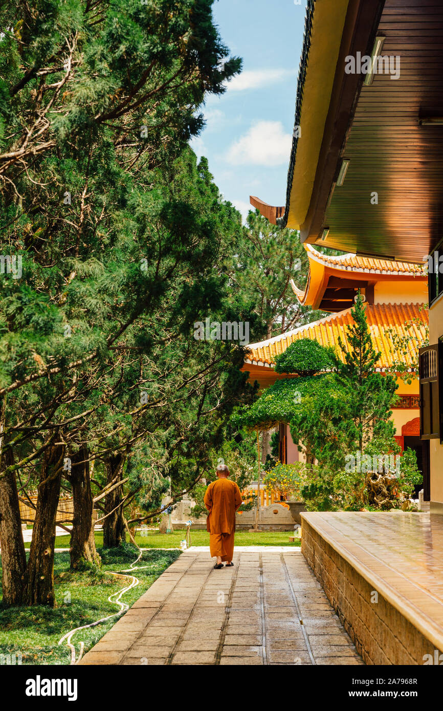 A monk walking through the grounds of the Truc Lam monastery located on a hill near Dalat, Vietnam Stock Photo