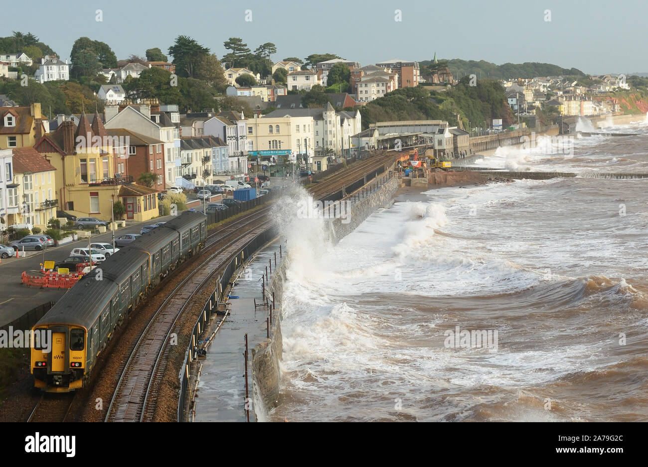 Rough sea at Dawlish as a diesel multiple unit arrives from Paignton. Stock Photo