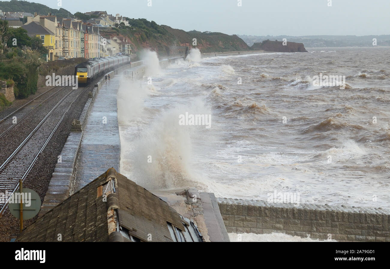 Rough sea at Dawlish as a Cross Country high speed train passes two joggers on the sea wall. Stock Photo