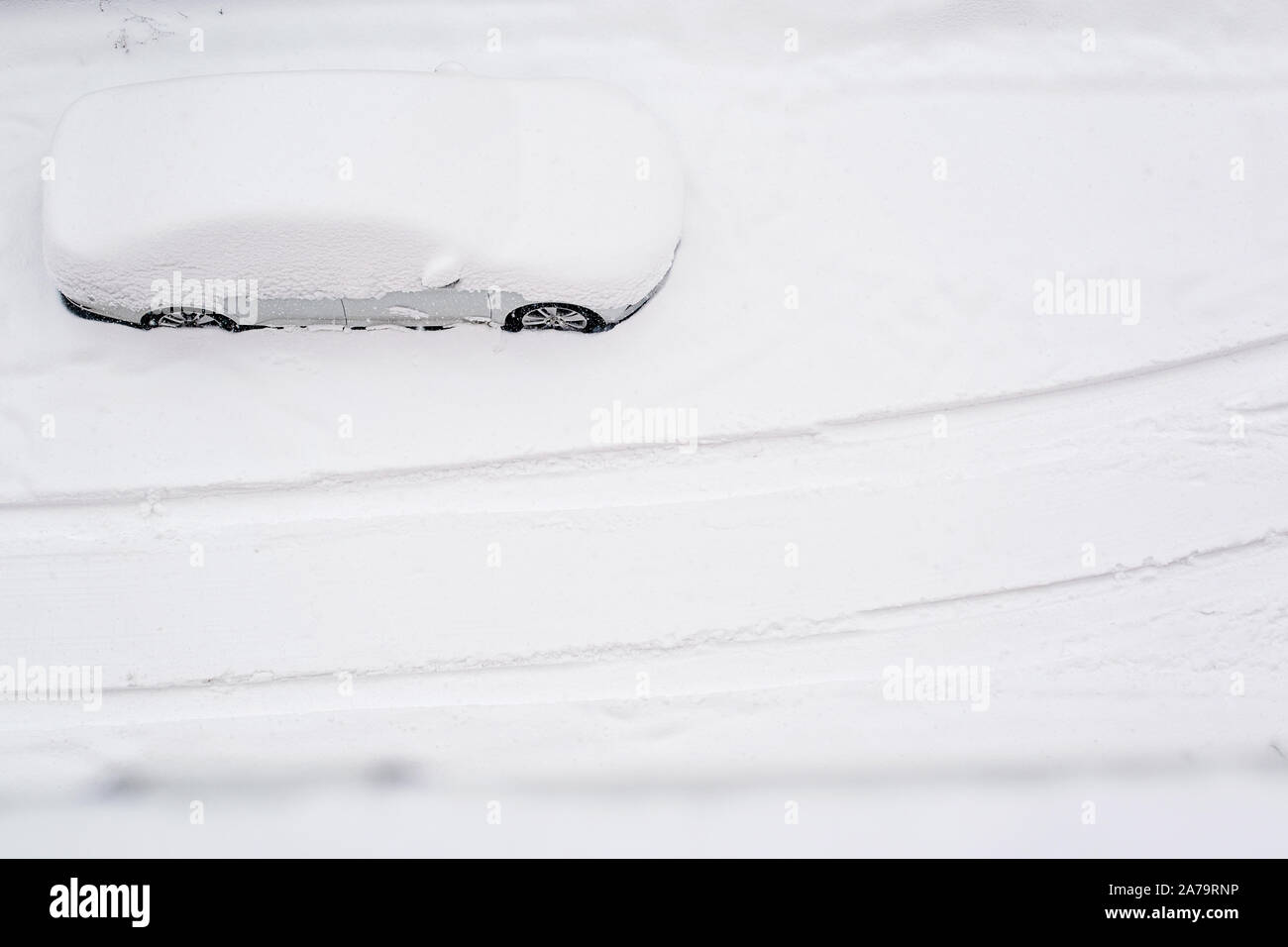 Top view on silver car burried in snow on the road after blizzard. Heavy snow in the city. After snow storm. Copy space. Snow storm. Space for text. Stock Photo
