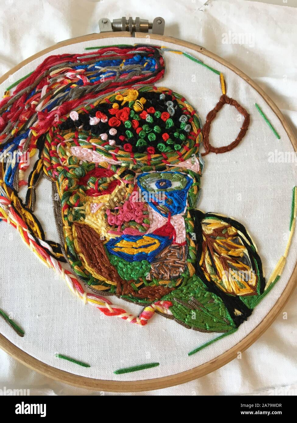 Homeless asyum seeker handsewn concept on circular wooden hoop using DMC embroidery stitching threads.Red cross, Sweden.Work in progress-mobile pic(1) Stock Photo