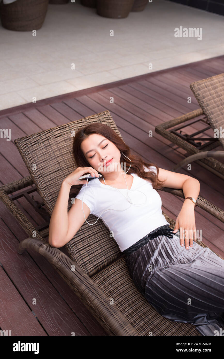 summer holidays, woman relaxing while listening to music and siiting in deckchair Stock Photo
