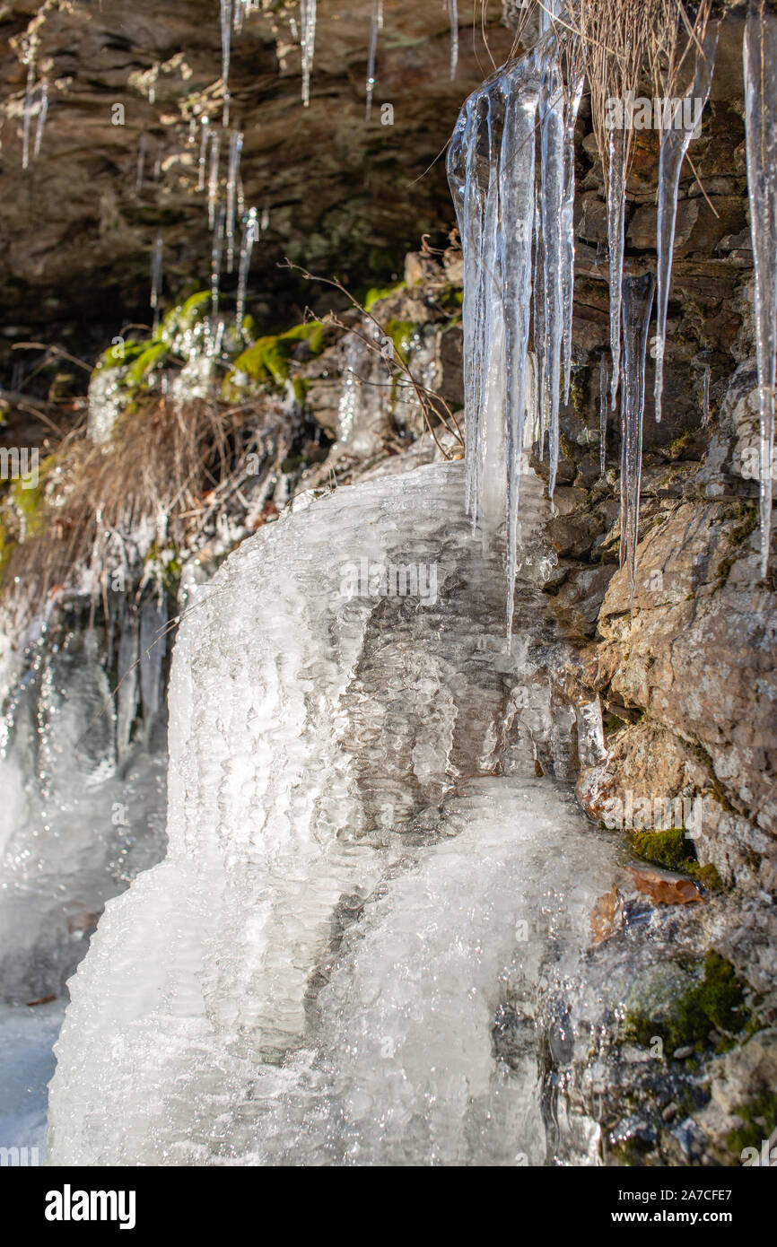 Rocks under ice layers,  phantasmagoric ice shapes, frozen leaves, grass. Czech mountains. Stock Photo