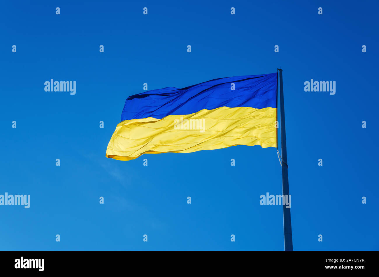 Ukrainian flag flying on a flagpole in against the blue sky on a warm summer day Stock Photo