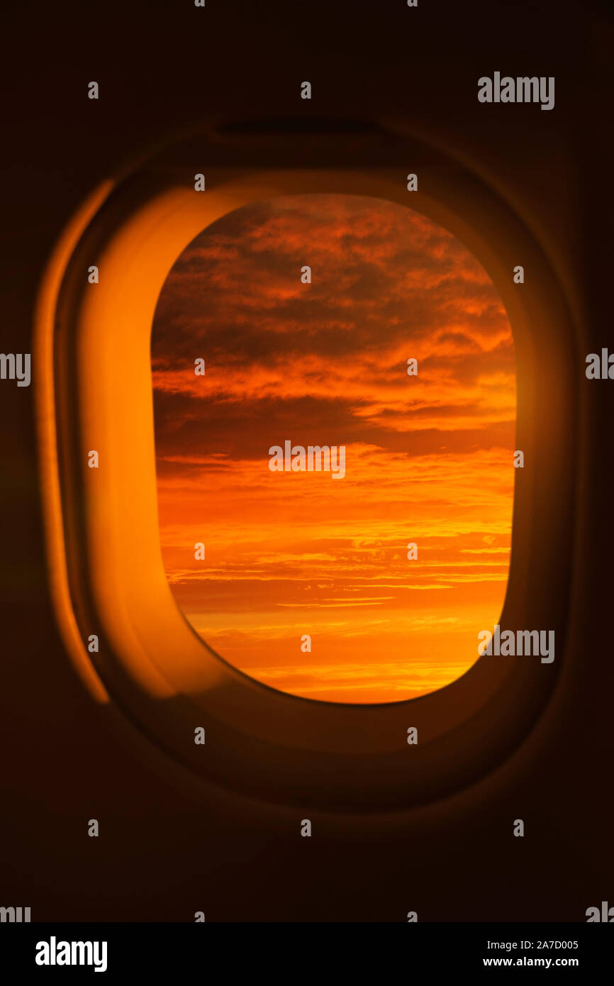 View out of an airplane window of a bright red sunset Stock Photo
