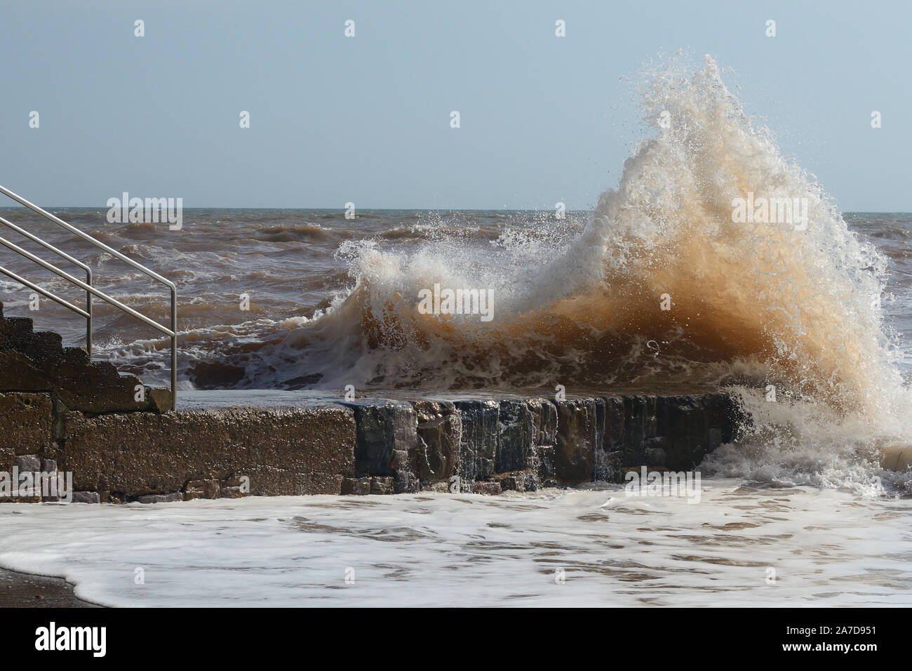 Waves crashing over a breakwater at Dawlish during high tide. Stock Photo