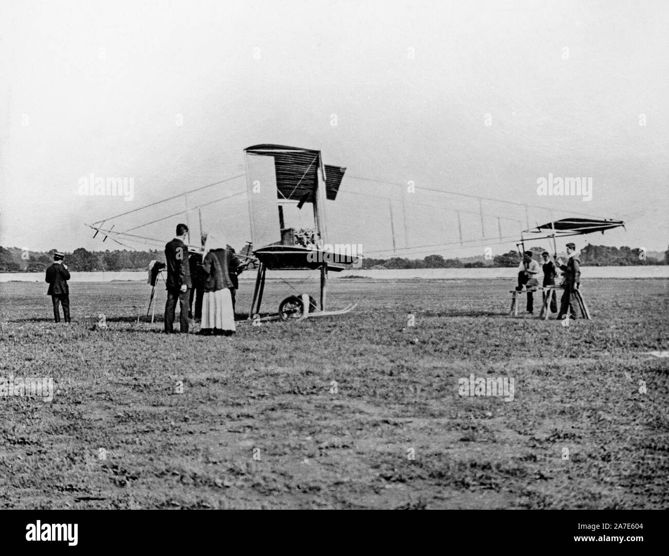 A vintage black and white photograph from 1910, showing a Neale VII Biplane, being prepared for take off, with some people watching. Stock Photo