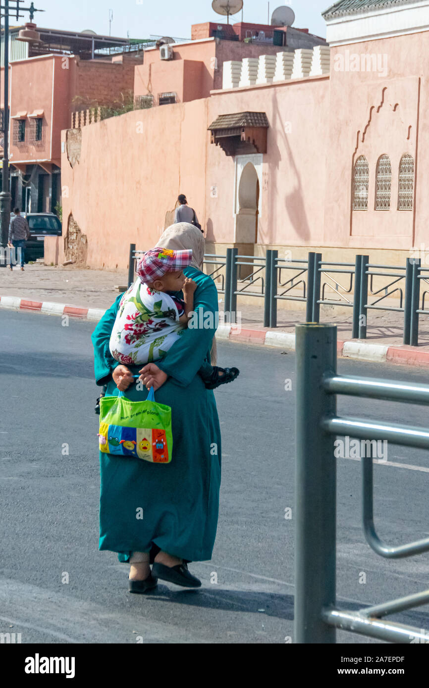 Arab woman with child behind her back in the city of Marrakech. Morocco October 2019 Stock Photo