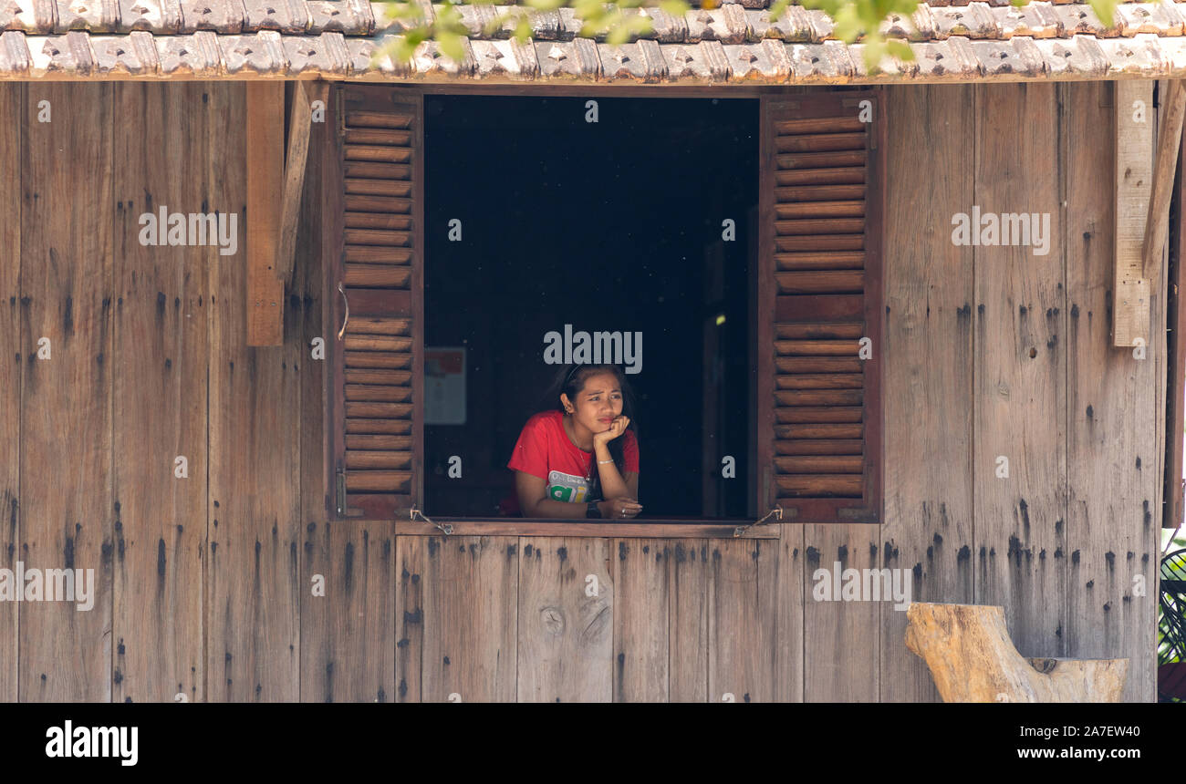 Vietnam Phu Quoc island 2 April 2019. Vietnamese girl waitress from the cafe sad and looks out the window Stock Photo