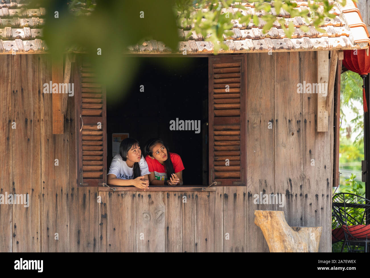 Vietnam Phu Quoc island 2 April 2019. two waitress girls look cautiously out the open window of the cafe from the burning in the air Stock Photo