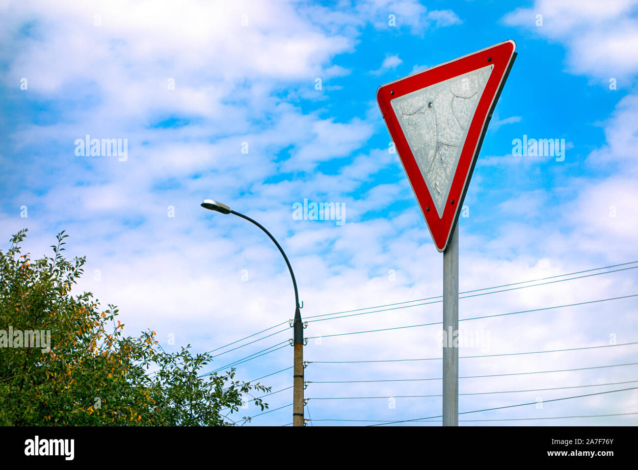 Give way road sign against cloudy sky. Stock Photo