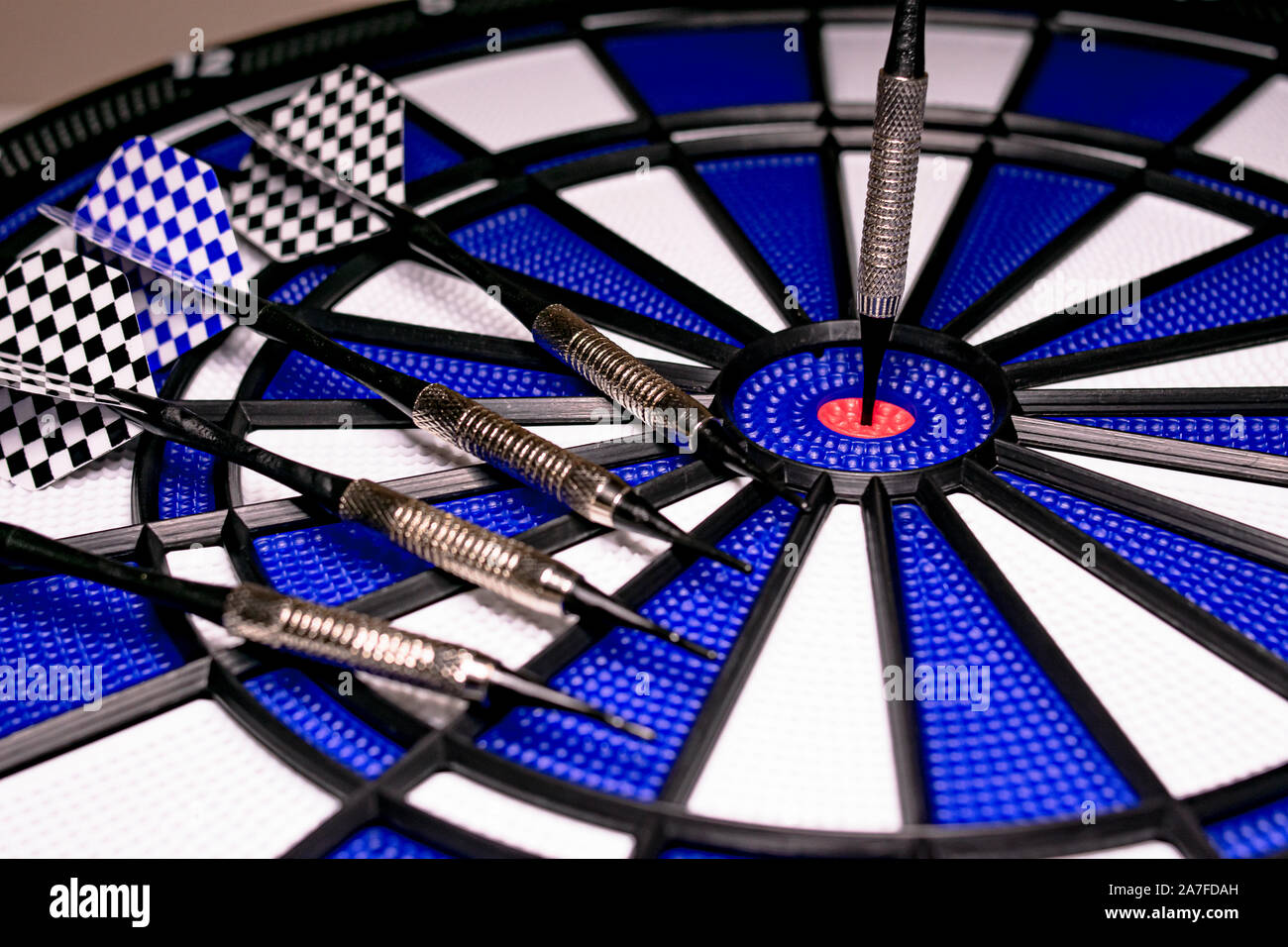 Traditional game of darts composed of target and darts in white and blue colors, with central point in red, and plastic material to avoid dangers and Stock Photo
