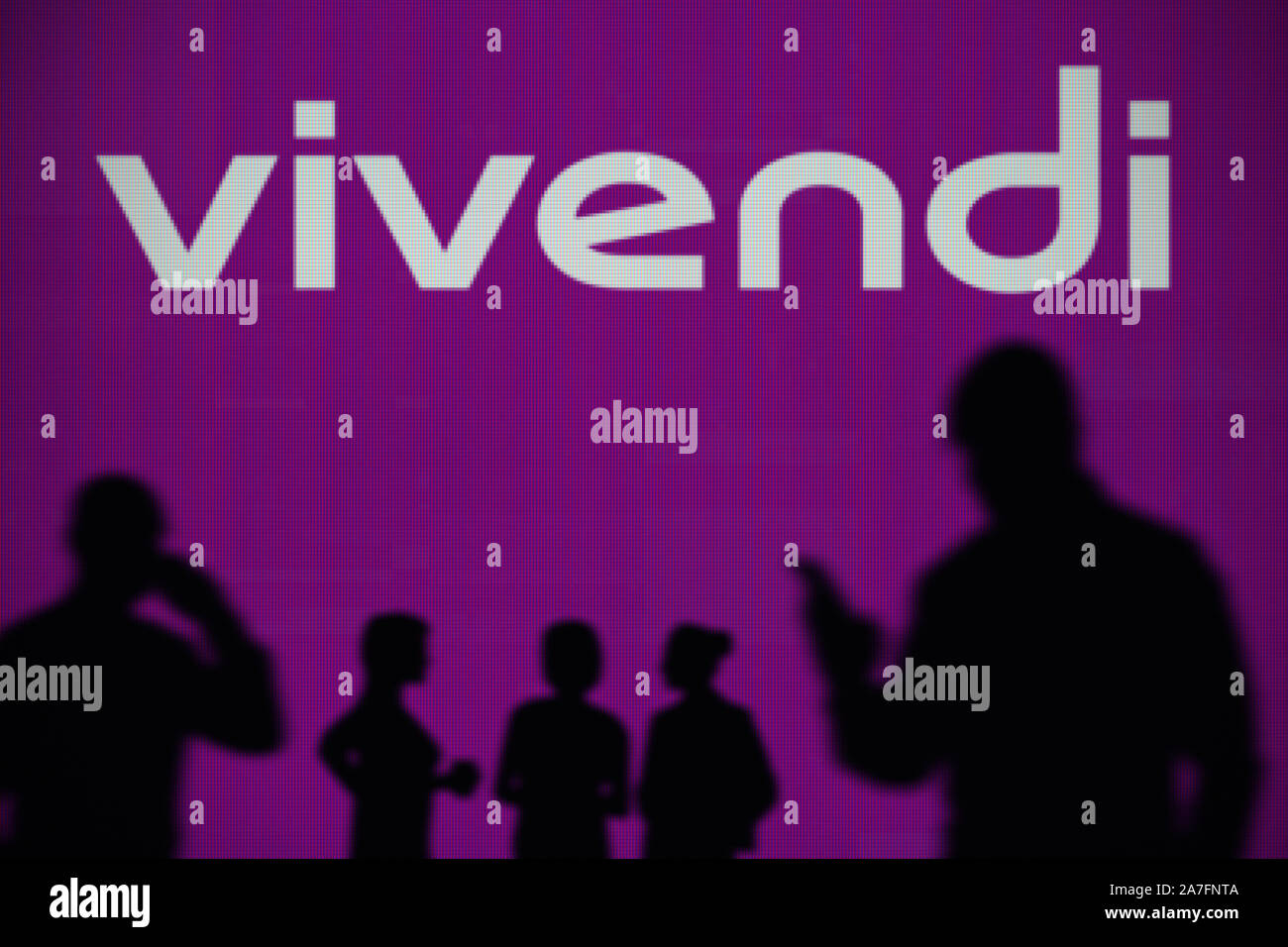 The Vivendi logo is seen on an LED screen in the background while a silhouetted person uses a smartphone (Editorial use only) Stock Photo