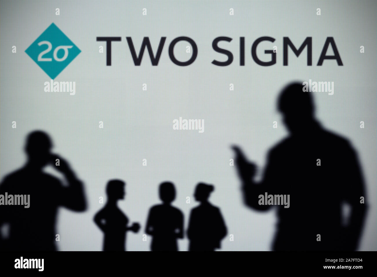 The Two Sigma logo is seen on an LED screen in the background while a silhouetted person uses a smartphone (Editorial use only) Stock Photo