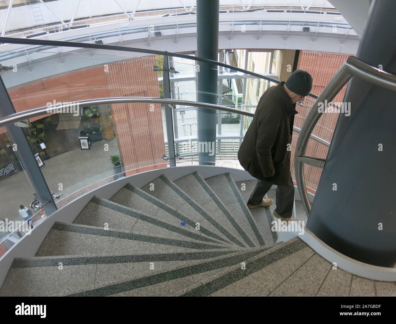 Man in woolly hat and brown winter jacket walking down the steps of the spiral staircase at the Victoria Gate shopping centre in Belfast city centre. Stock Photo