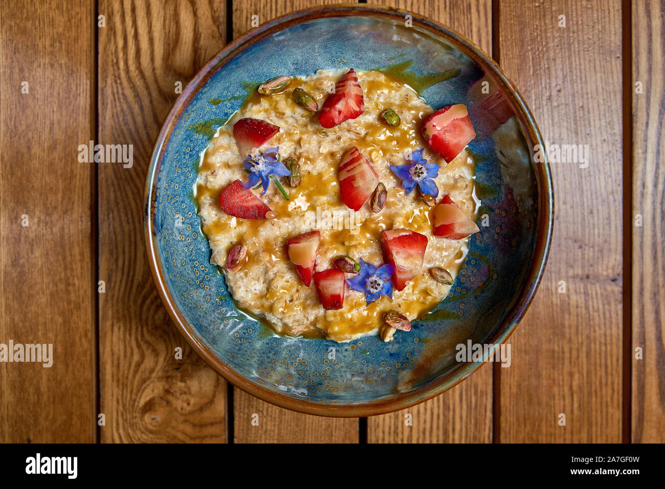 Granola for breakfast with berries and caramel. Oatmeal flakes or granola with strawberries. The concept of diet, healthy eating and eating. Top view, Stock Photo