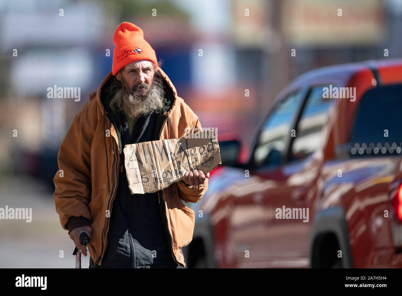 Homeless man panhandles for money at a busy intersection near a homeless encampment under a highway overpass days before a threatened crackdown by Texas Governor Greg Abbott on public right-of-way camping. Stock Photo