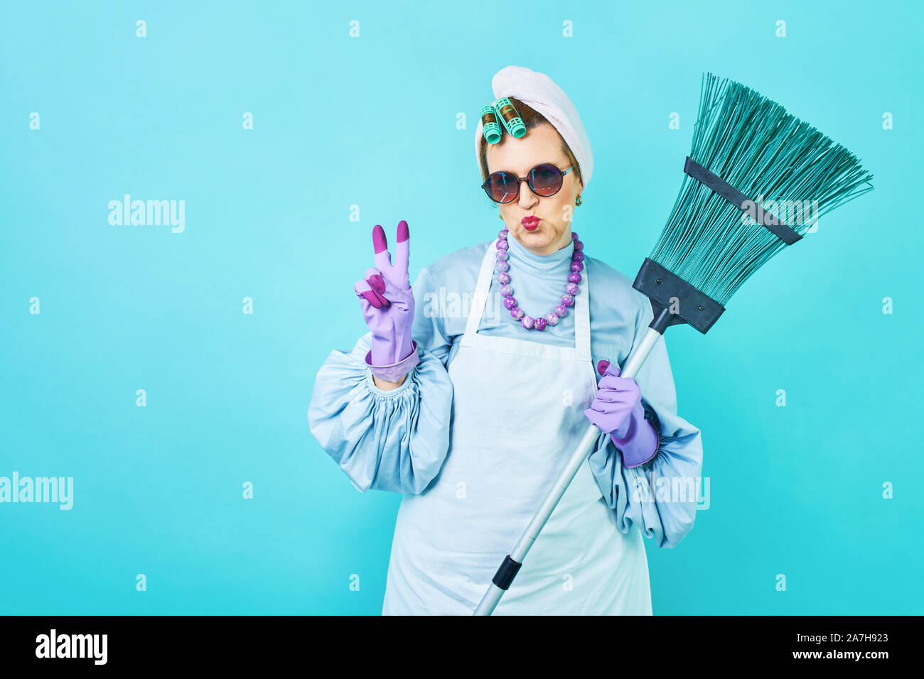 Cleaning Lady Fun. Elderly funny housewife fooling around with a broom. Full body isolated blue. Comical cleaning lady, old woman funky Stock Photo