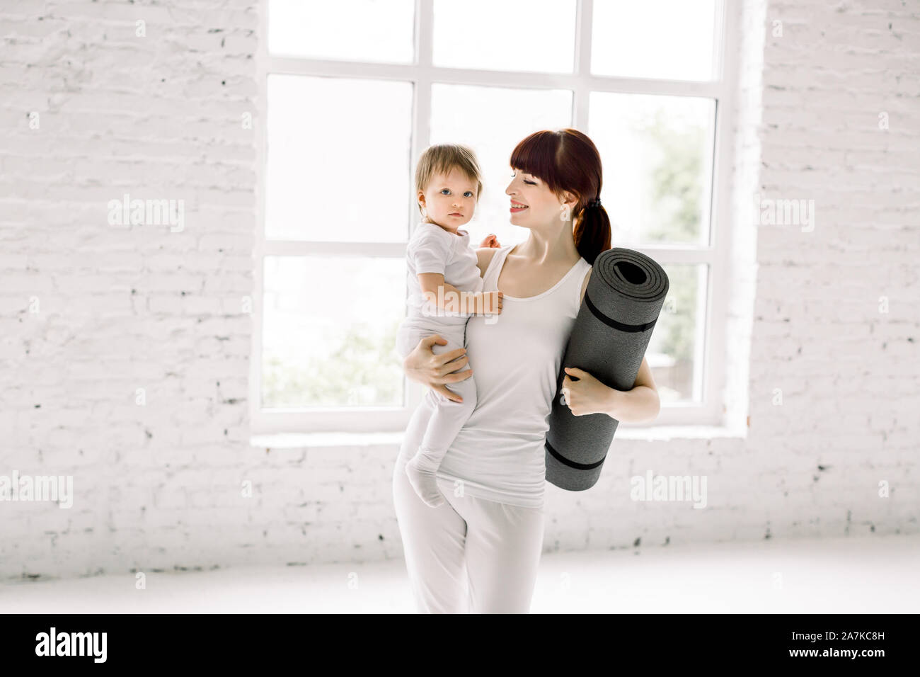 Sportive pretty young mother with little baby girl in white sport wear and yoga mat in hands, standing in light gym hall. Fitness, happy maternity and Stock Photo