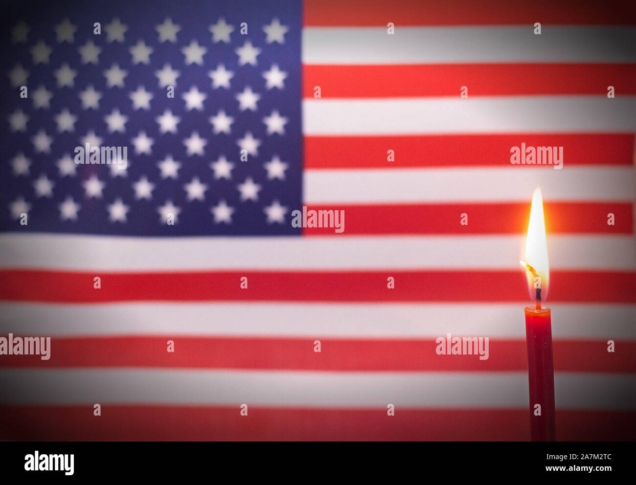 Burning candle on the background of the flag of Usa. The concept of mourning and sorrow in the country Stock Photo