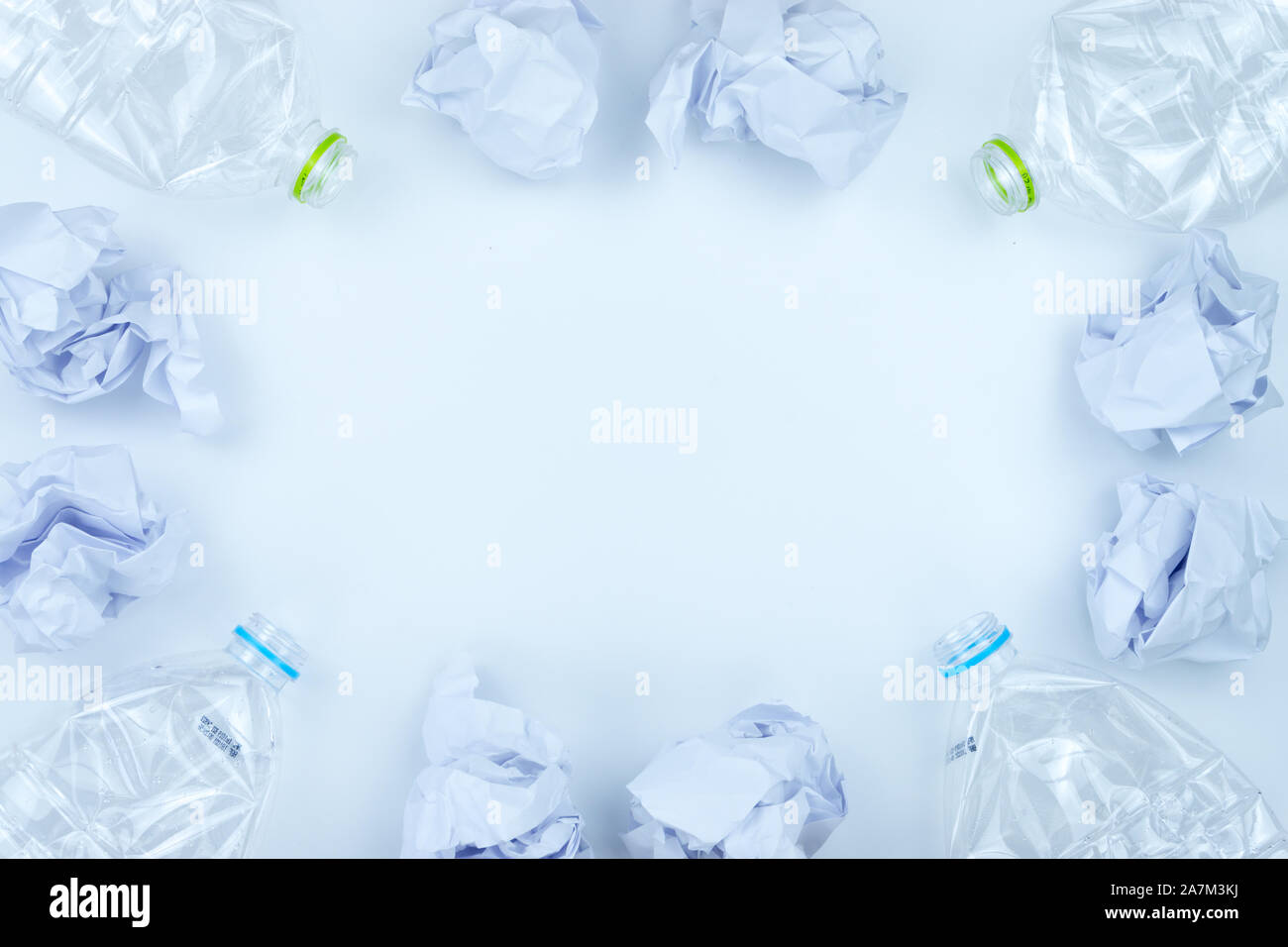 Recycling. The frame of used plastic bottle and crumpled paper on white background with copy space. Recycle and reuse concept Stock Photo