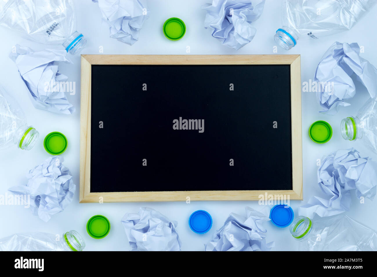Recycling. The frame of used plastic bottle, blackboard and crumpled paper on white background with copy space. Recycle and reuse concept Stock Photo