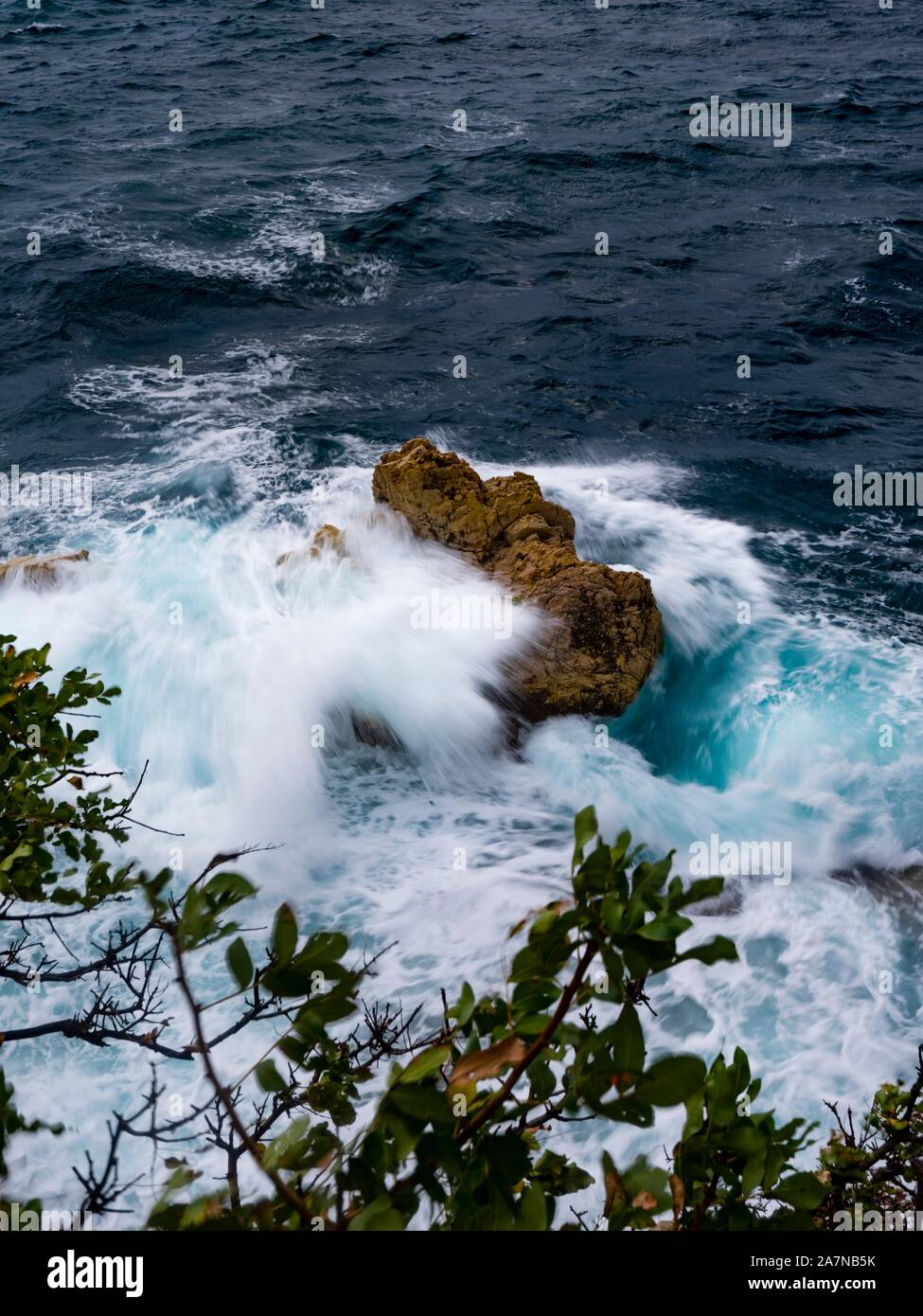 Longish exposure intentionally blurry big wave waves pushing over boulder rock in sea view from above Stock Photo