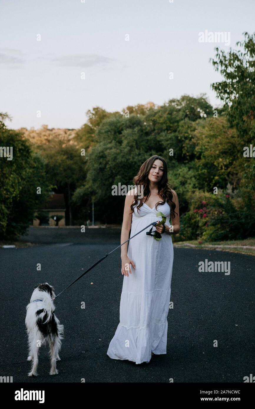 Pregnant woman white dress walking her dog Stock Photo