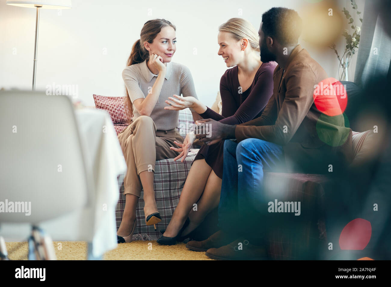 Full length view at group of modern young people chatting while sitting on cozy sofa at Christmas party, copy space Stock Photo
