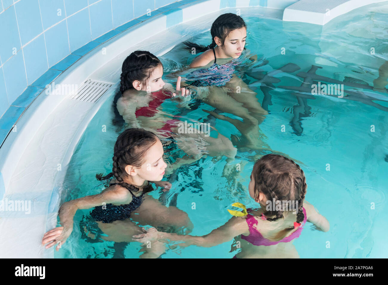 Girls swim in the pool. Happy girls play in the pool.Beautiful girls swim and having fun in water.Active holiday. Stock Photo
