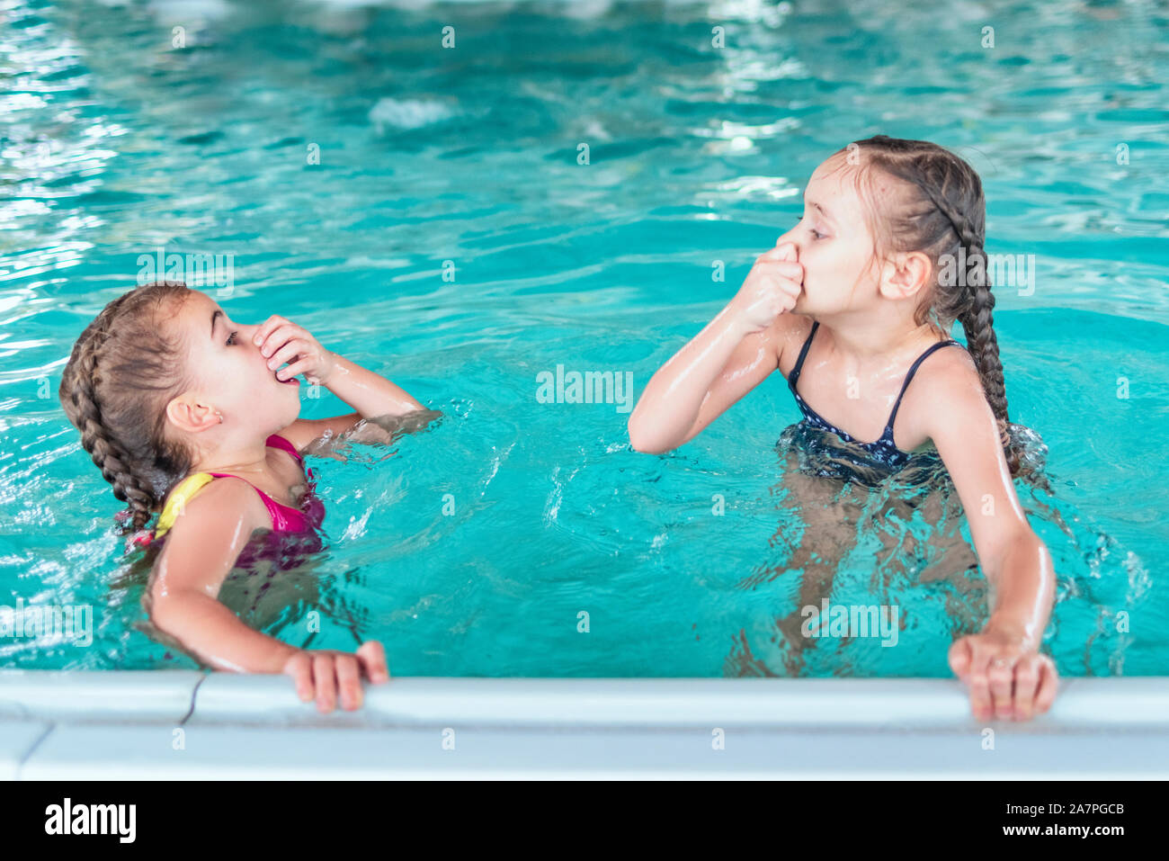 Two little girls swim in the pool. Two friends in the pool.Children playing in pool. Two little girls having fun in the pool. Stock Photo