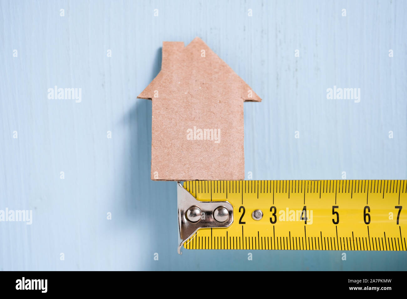 Cardboard cutout house on metal measuring tape on wooden blue background. Concept of surveying, budgeting, repairing. Stock Photo