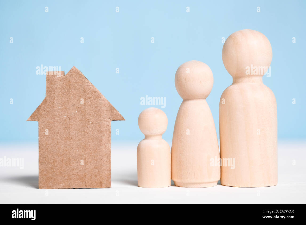 Wooden figures family with cardboard cutout house on blue background. Concept of moving to new home, settlement, rental, mortgage, eviction. Stock Photo