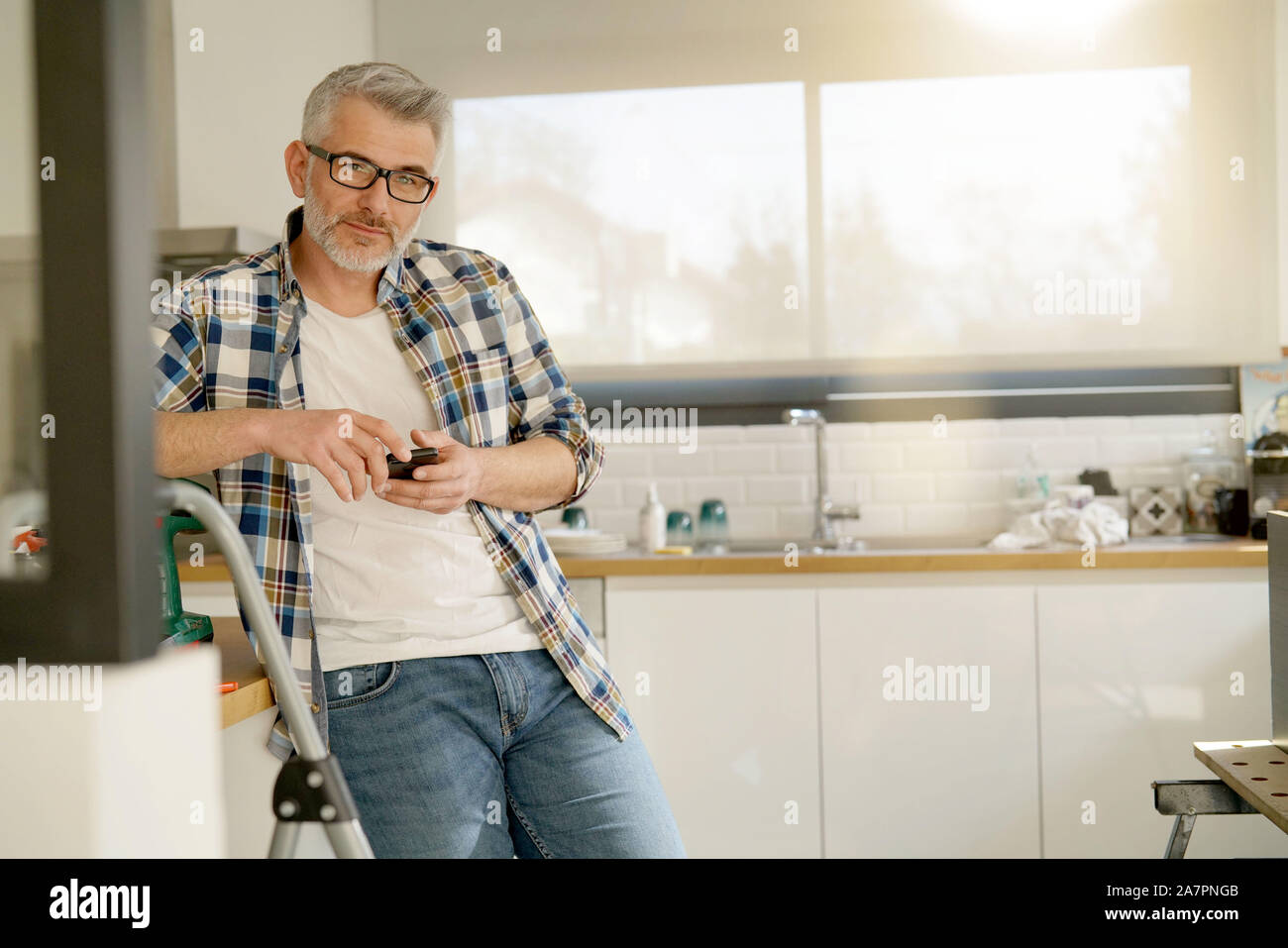 Mature handyman looking at camera leaning on ladder in modern kitchen Stock Photo