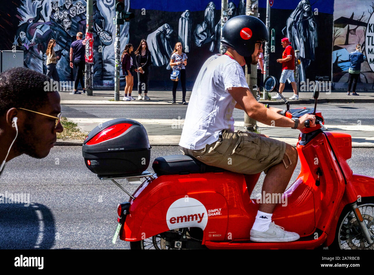 Berlin wall, man on rental scooter Emmy passing in Muhlenstrasse, East Side Gallery Germany Stock Photo