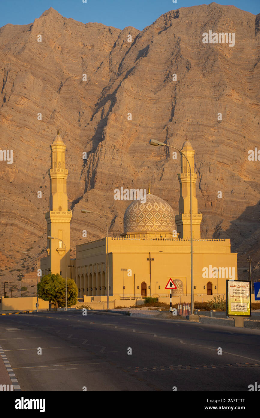 Sultan Qaboos Mosque in Bukha, Musandam, Oman at sunset with the beautiful mountains and blue sky in background. Stock Photo