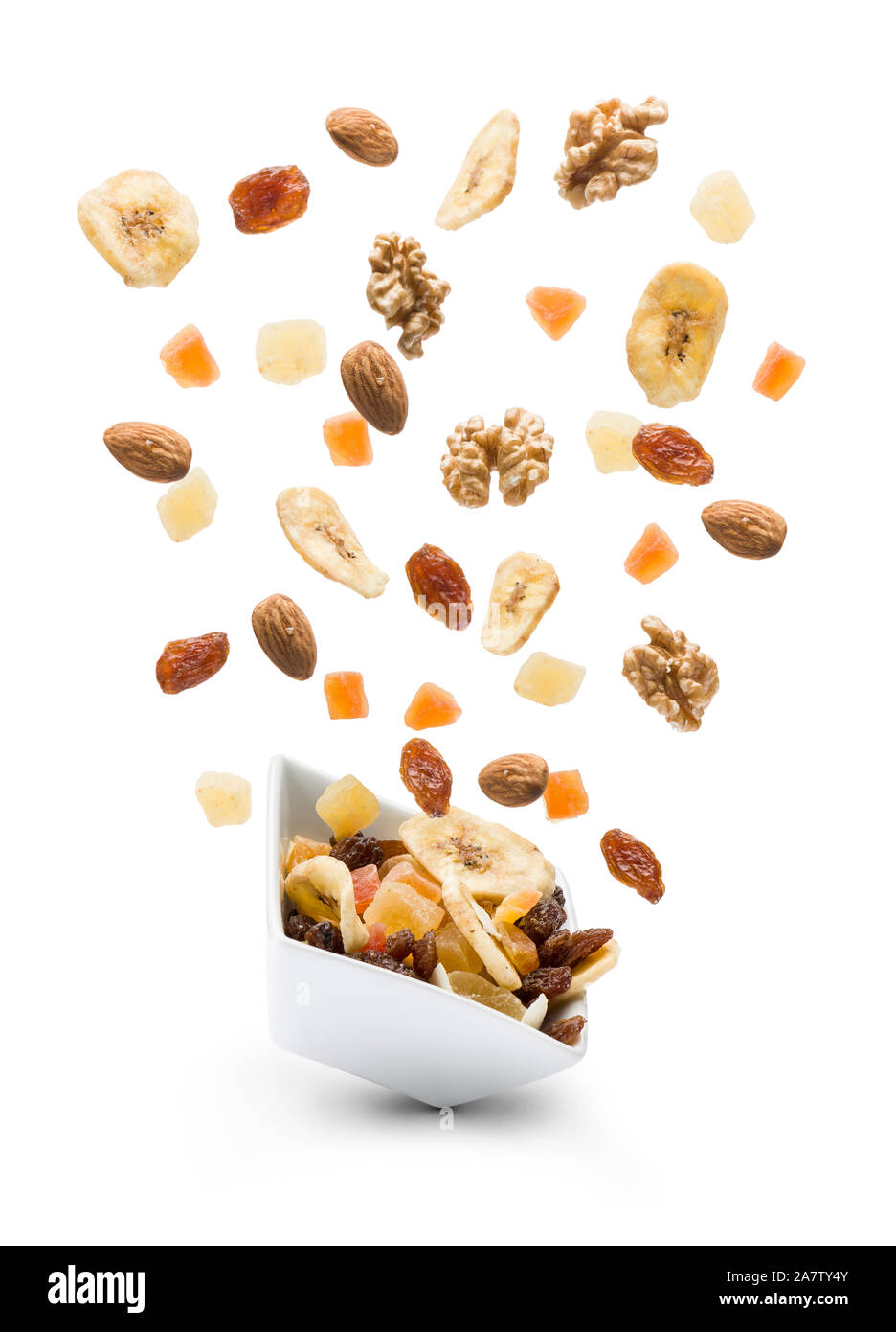Dried fruits jumping out white bowl on white background Stock Photo