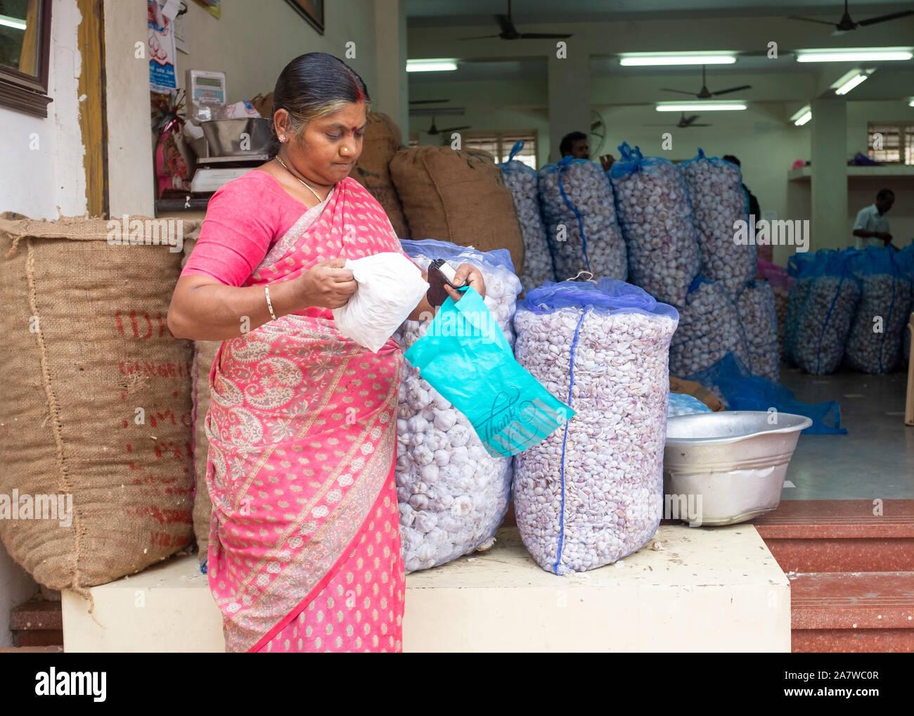 Woman buying garlic in shop, Trichy, Tamil Nadu, India Stock Photo