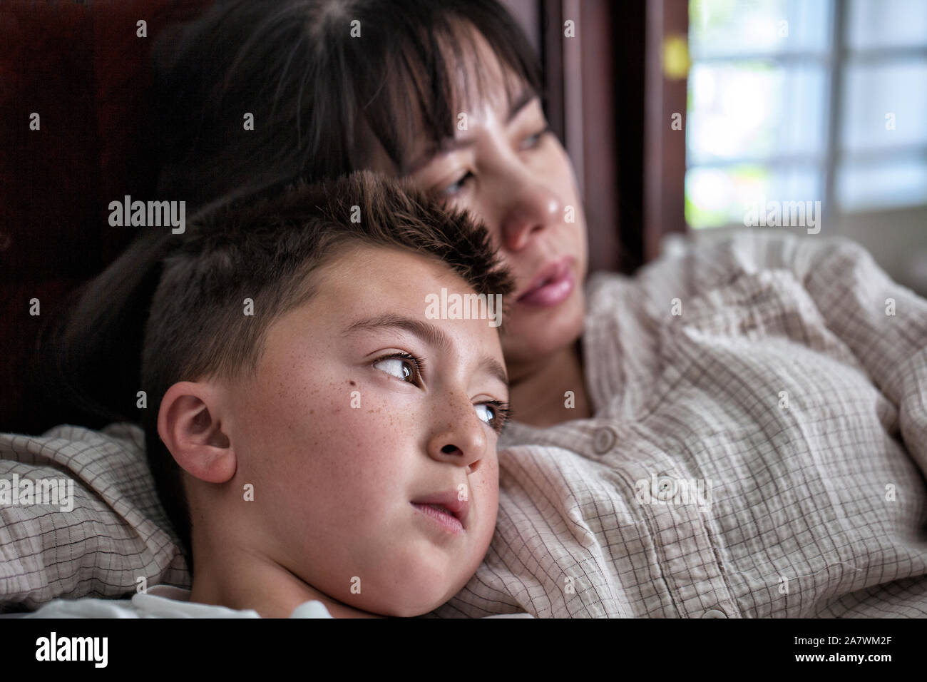 Asian Vietnamese woman laying in bed with her mixed race Asian Caucasian son staring out the window with sad  expressions Stock Photo