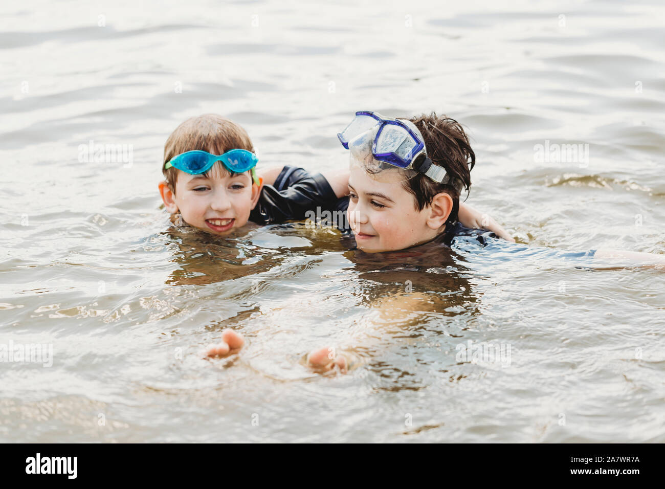 Brothers wearing swimming goggles in water hugging Stock Photo